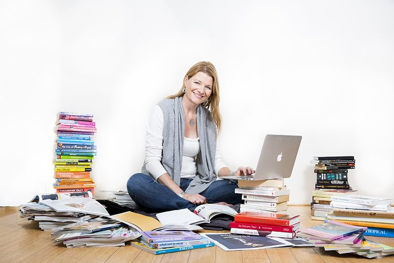 girl working on the floor with a pile of books headshot