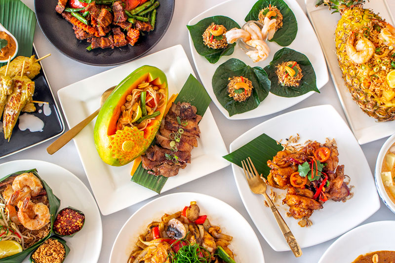 commercial product food photograph of thai dishes on a table